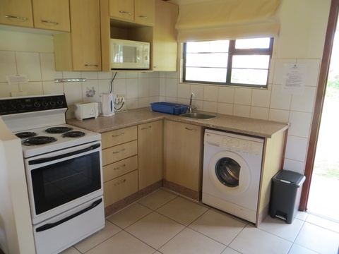 Kitchen area of Cottage 56 with a washing machine - Seaside Cottages Fish Hoek
