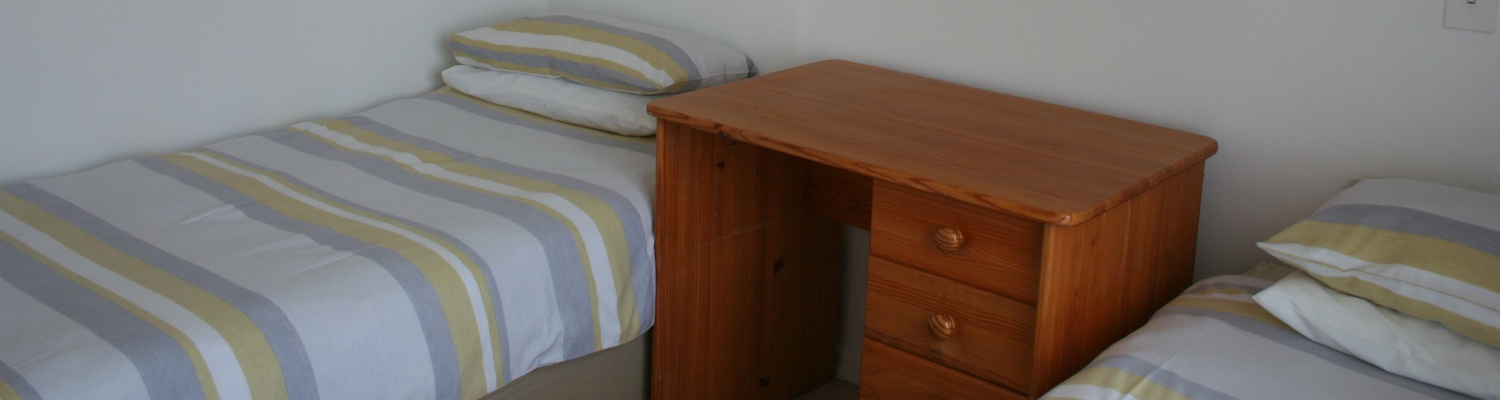 Main bedroom with twin beds of Cottage 44 at Seaside Cottages Fish Hoek